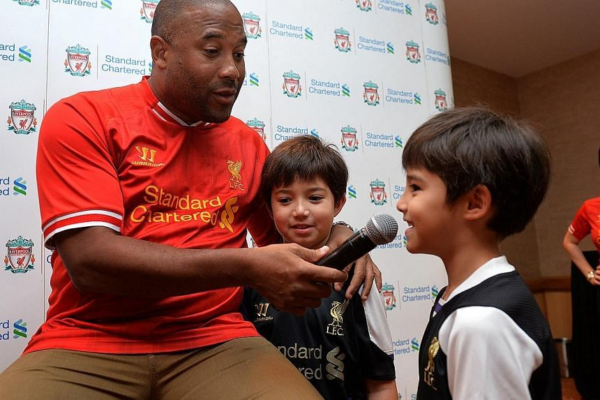 Liverpool legend John Barnes jokes with Liverpool fans Patrick Brice (centre) and his brother Matthew (second from right) at a meet-and-greet session in Swissotel the Stamford, on 30 Nov 2013.-- ST PHOTO:CAROLINE CHIA