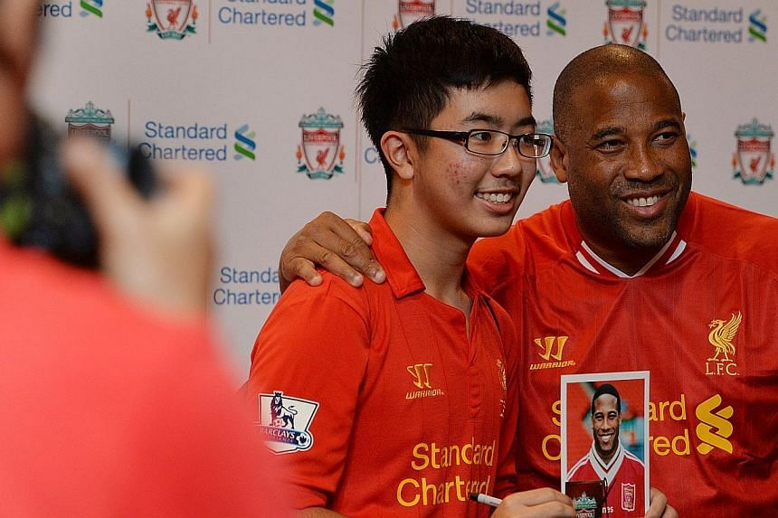 Benjamin Lew, 15, poses for photos with Liverpool legend John Barnes. -- ST PHOTO: CAROLINE CHIA