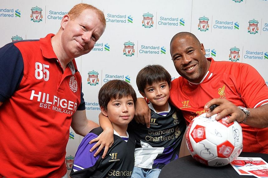 (From left to right) Steve Brice and his sons Patrick, 8, and Matthew, 7, pose for a photo with Liverpool legend John Barnes. -- ST PHOTO: CAROLINE CHIA