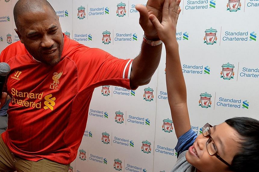 Liverpool legend John Barnes gives a high-five to Cohen Wee, 7. -- ST PHOTO: CAROLINE CHIA