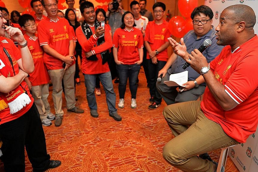 Liverpool legend John Barnes (right) speaks to Liverpool fans who were surprised to see the former player in person in Singapore.-- ST PHOTO:CAROLINE CHIA