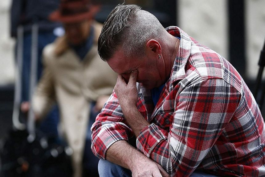 Paul Watt, a regular at the Clutha pub, reacts at the police cordon set up around the site of a helicopter crash on the Clutha in the centre of Glasgow, Scotland, on Nov 30, 2013.Pubgoers inside The Clutha bar in Glasgow told on Saturday how th