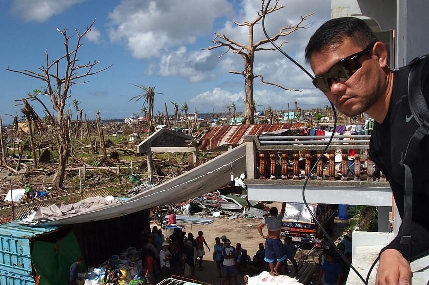 Mr Julian Tan surrounded by a scene of devastation in Guiuan. His Singapore-Philippine team managed to deliver all their relief supplies to Ormoc city, Tacloban city and Guiuan in just four days, while others encountered obstacles. -- ST PHOTO: JOYCE