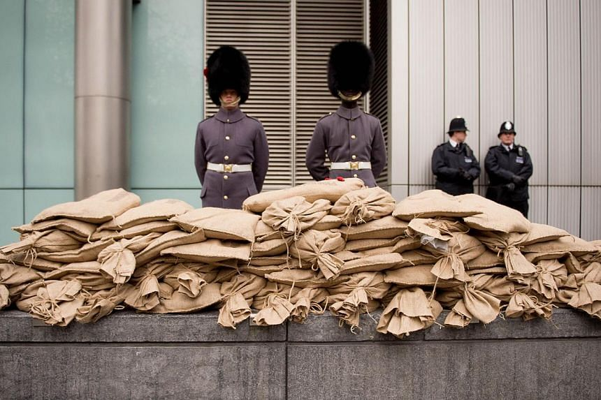 """Soldiers stand guard next to sacks of """"sacred soil"""" taken from First World War battlefields, as the Household Cavalry Mounted Regiment prepare to take part in the ceremonial procession to transport it to the site of the Flanders Fields memorial garde"""