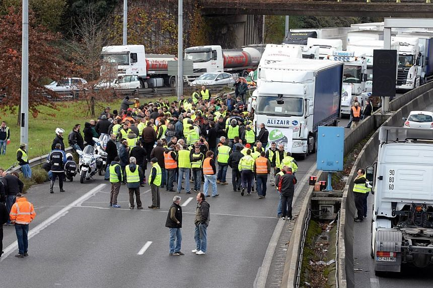 Dozens of drivers stand in front of their trucks as they blocked a motorway at the Paris-Lyon connection, during a demonstration near the French southwestern town of Lormont, to protest against government's controversial plans for a tax on heavy vehi