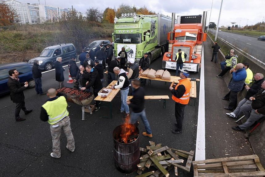 Trucks drivers share a lunch as they block the motorway during a demonstration to protest against government's controversial plans for a tax on heavy vehicles on Nov 30, 2013, in Roissy-en-France outside Paris. -- PHOTO: AFP