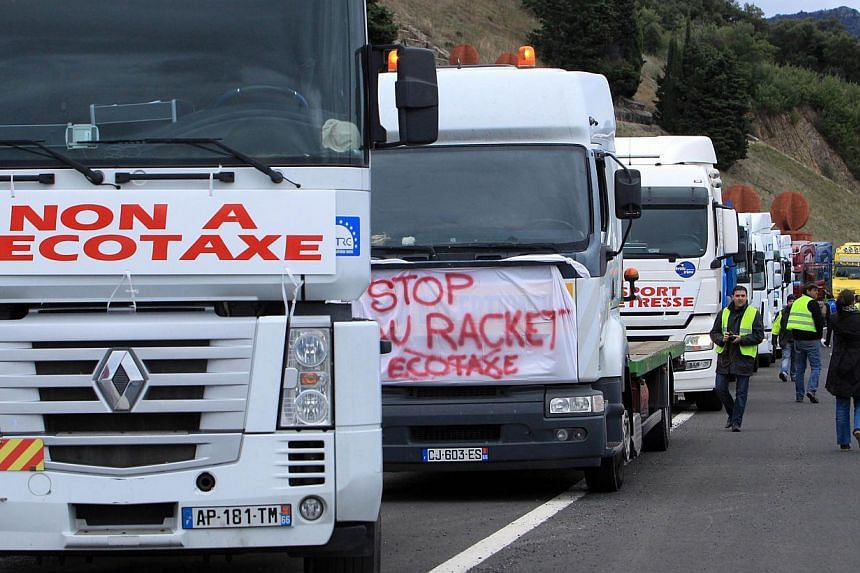 Truck drivers walk in front of their vehicles on highway A9 at the French-Spanish border to demonstrate against government's controversial plans for a tax on heavy vehicles on Nov 30, 2013, in Le Perthus . -- PHOTO: AFP