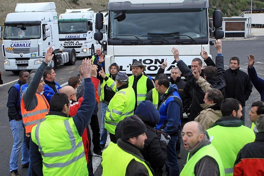 Truck drivers gather in front of their vehicles on highway A9 at the French-Spanish border to demonstrate against government's controversial plans for a tax on heavy vehicles on Nov 30, 2013 in Le Perthus. -- PHOTO: AFP