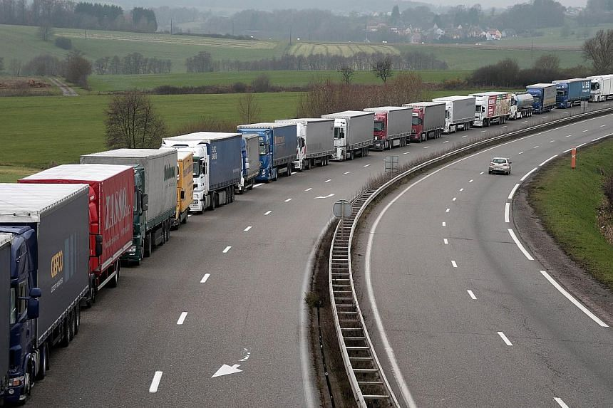 Dozens of foreign truck drivers are blocked in a mototway during a demonstration near Phalsbourg, eastern France, to protest against government's controversial plans for a tax on heavy vehicles on Nov 30, 2013. -- PHOTO: AFP