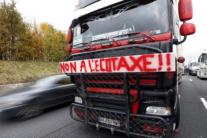 Dozens of trucks block the motorway during a demonstration to protest against government's controversial plans for a tax on heavy vehicles on Nov 30, 2013, in Roissy-en-France outside Paris. -- PHOTO: AFP