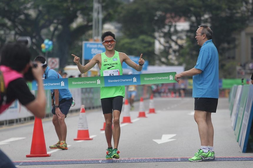 Singapore's Mok Ying Ren crosses the finish line and becomes the fastest local runner for the 42.195km Standard Chartered Marathon 2013 on Dec 1, 2013. -- ST PHOTO: KEVIN LIM
