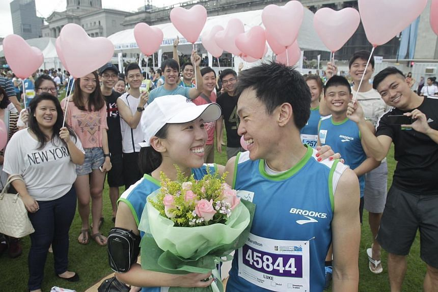 Shipping analyst Ng Ling Fong, 28, proposes to girlfriend Melissa Ho, a 25-year-old public servant, and succeeds after their run in the Standard Chartered Marathon 2013 Dec 1, 2013. -- ST PHOTO: KEVIN LIM
