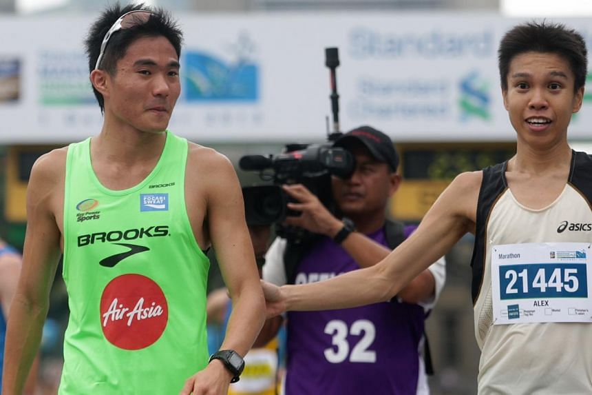 Singapore's Mok Ying Ren crosses the finish line and becomes the fastest local runner for the 42.195km Standard Chartered Marathon 2013 Dec 1, 2013.. With him is local runner Alex Ong. -- ST PHOTO: KEVIN LIM