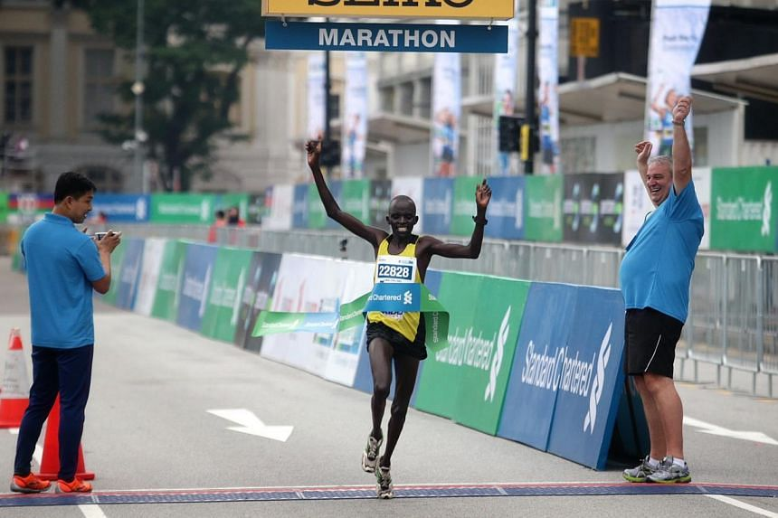 Kenya's Chelimo Luka Kipkemoi crosses the finish line and becomes the fastest man for the 42.195km Standard Chartered Marathon 2013 Dec 1, 2013. -- ST PHOTO: KEVIN LIM
