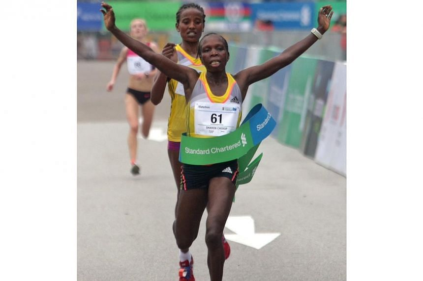 Kenya's Sharon Cherop crosses the finish line and becomes the fastest woman ahead of countrywoman Debre Godana and Russian Prokopeva Alina for the 42.195km Standard Chartered Marathon 2013 Dec 1, 2013. -- ST PHOTO: KEVIN LIM