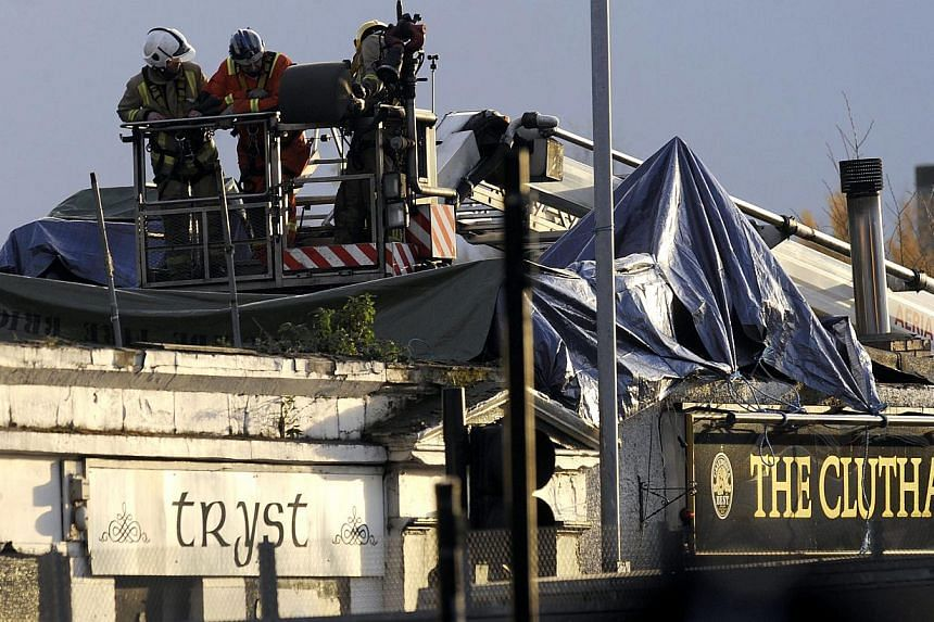 Emergency services personnel inspect the rooftop of a pub where a police helicopter crashed in Glasgow on Nov 30, 2013. The pubs were festooned with flags for Scotland's Saint Andrew's Day festivities, but a day after a police helicopter made a fatal