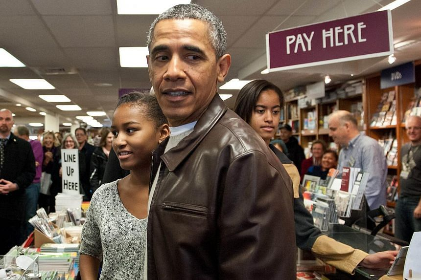US President Barack Obama and daughters Malia (right) and Sasha (left) leave the Politics and Prose bookstore in Washington on Nov 30, 2013 after buying books as part of Small Business Saturday. -- PHOTO: AFP