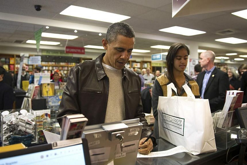 US President Barack Obama shops with his daughter Malia at Politics and Prose Bookstore and Coffeehouse in Washington Nov 30, 2013. -- PHOTO: REUTERS