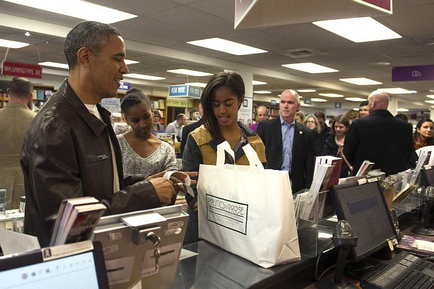 US President Barack Obama shops with daughters Sasha and Malia at Politics and Prose Bookstore and Coffeehouse in Washington on Nov 30, 2013. -- PHOTO: REUTERS