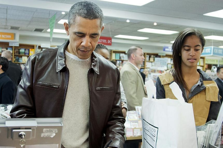 President Barack Obama, with daughters Sasha, center partially hidden, and Malia, pays for his purchase the the local bookstore Politics and Prose in northwest Washington, on Saturday, Nov 30, 2013. -- PHOTO: AP