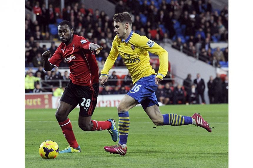 Cardiff City's Kevin Theophile-Catherine challenges Arsenal's Aaron Ramsey (right) during their English Premier League soccer match at Cardiff City Stadium in Cardiff, Wales, on Nov 30, 2013. Aaron Ramsey indulged his new goalscoring habit on his ret