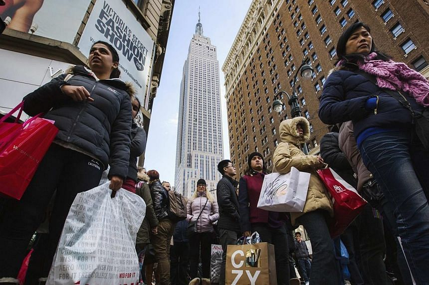 Pedestrians stand with shopping bags as they wait to cross a street during Black Friday sales in New York, on Friday, Nov 29, 2013. Online US shopping for Black Friday deals soared to US$3 billion (S$3.8 billion) during a two-day period beginnin