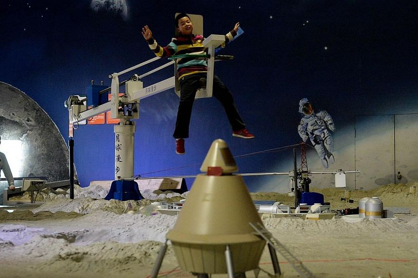 A Chinese boyrides a zero gravity device at theScience Museum in Beijing, China, on Sunday, Dec 1, 2013. -- PHOTO: AFP