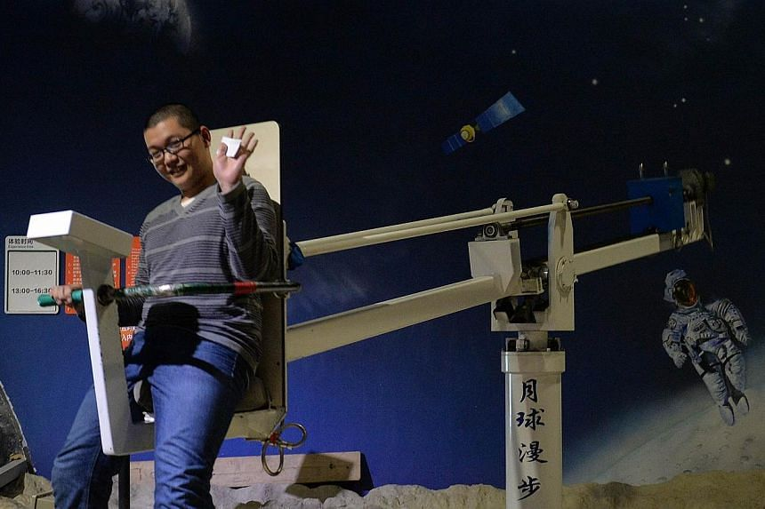 A Chinese man rides a zero gravity device at theScience Museum in Beijing, China, on Sunday, Dec 1, 2013. -- PHOTO: AFP