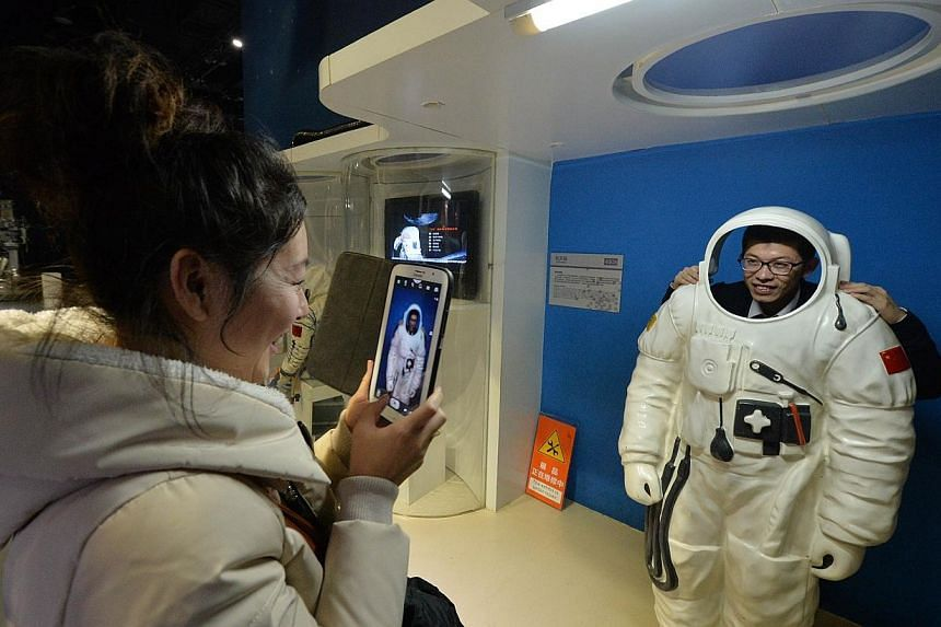A Chinese woman takes a photo of her husband in an astronaut (known locally as taikonauts) suit at the Science Museum in Beijing, China, on Sunday, Dec 1, 2013. -- PHOTO: AFP