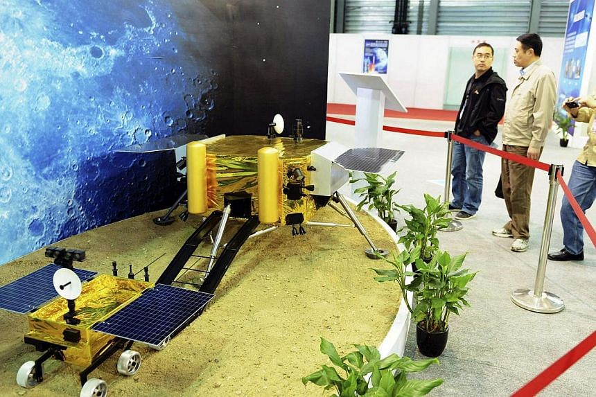 Visitors look at a model of a lunar rover driving out from a landing platform,at the China International Industry Fair 2013 in Shanghai, on Nov 5, 2013. -- FILE PHOTO: REUTERS