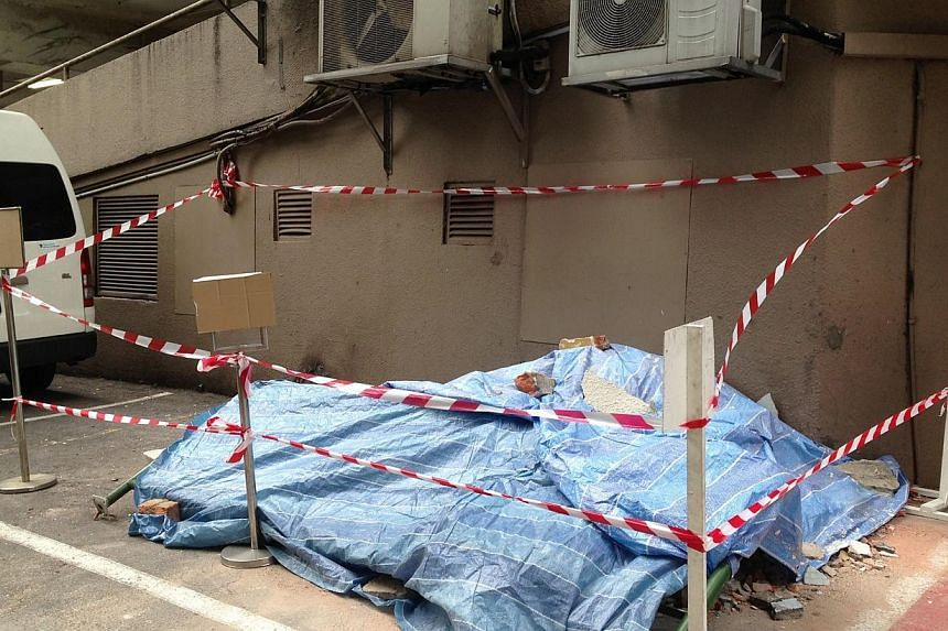 As of Sunday afternoon, the area with the pile of fallen concrete was covered and sealed off. -- ST PHOTO: AMELIA TENG