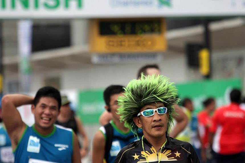 A full marathon participant by the moniker of Greeneyes Val crosses the finish line during the Standard Chartered Marathon 2013 on Dec 1. -- ST PHOTO: KEVIN LIM