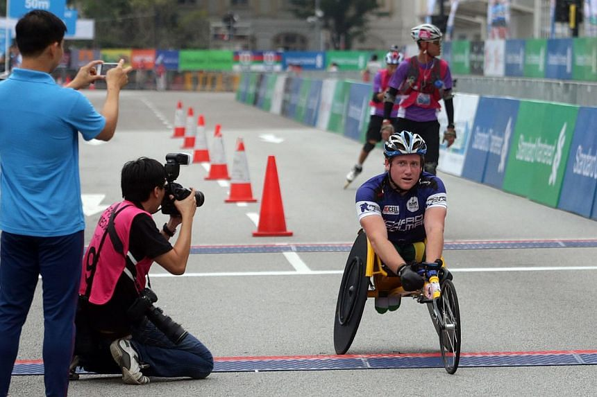Top racer on wheels crosses the line during the Standard Chartered Marathon 2013 on Dec 1. -- ST PHOTO: KEVIN LIM