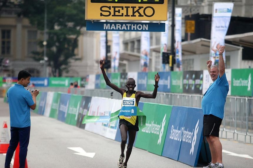 Kenya's Chelimo Luka Kipkemoi crosses the finish line and becomes the fastest man for the 42.195km Standard Chartered Marathon 2013 on Dec 1. -- ST PHOTO: KEVIN LIM