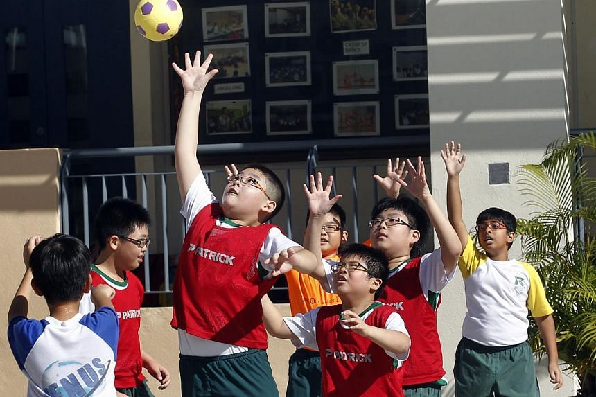Yio Chu Kang Primary pupils play handball during a PE lesson. The revamped PE curriculum will be introduced at the lower primary and secondary levels from next year. -- ST PHOTO: CHEW SENG KIM