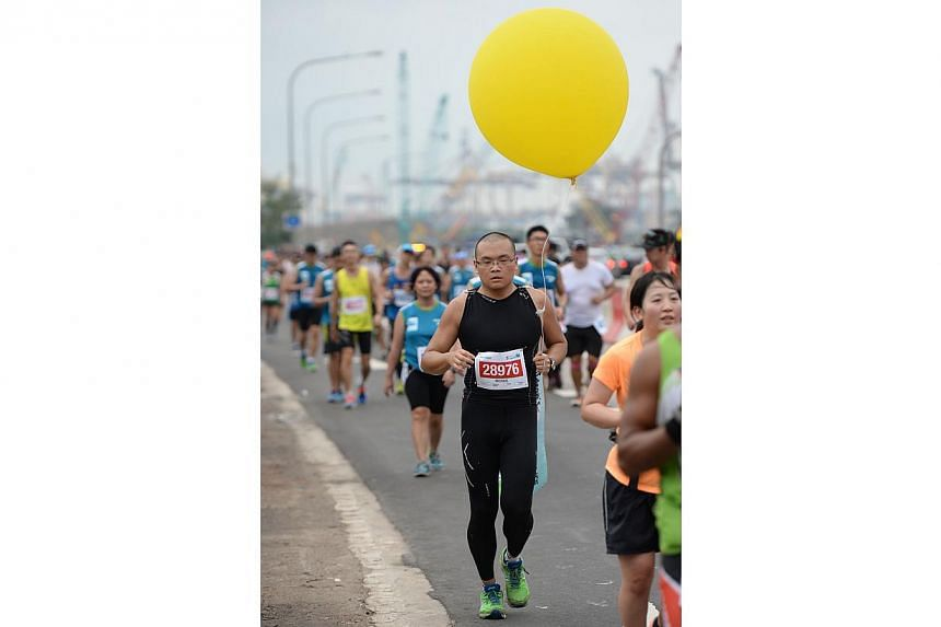 Michael Ng, 31, runs with a yellow balloon to raise awareness and to raise funds for Children's Cancer Foundation during the Standard Chartered Marathon 2013 on Sunday, Dec 1, 2013. -- ST PHOTO: RAJ NADARAJAN
