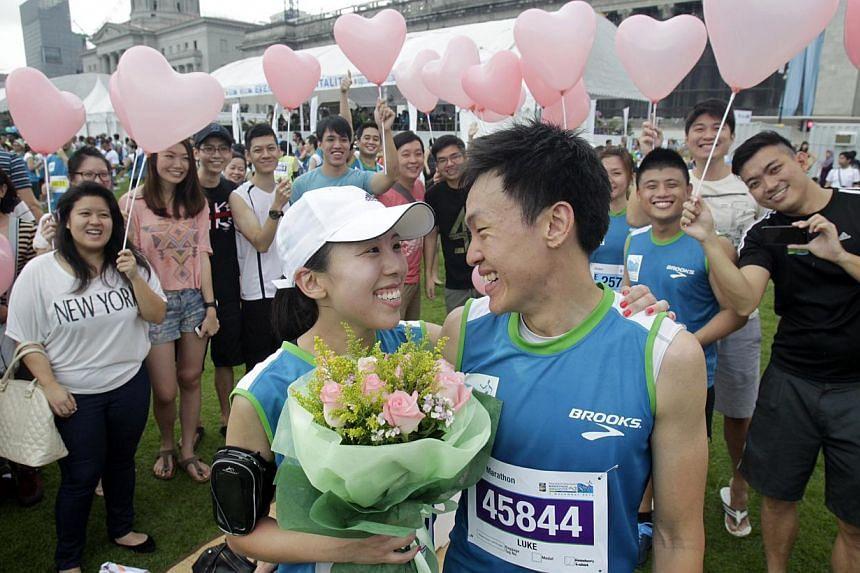Shipping analyst Ng Ling Fong proposes to girlfriend, Melissa Ho, a public servant, and succeeds after their run in the Standard Chartered Marathon Singapore on Sunday, Dec 1, 2013. -- ST PHOTO:KEVIN LIM