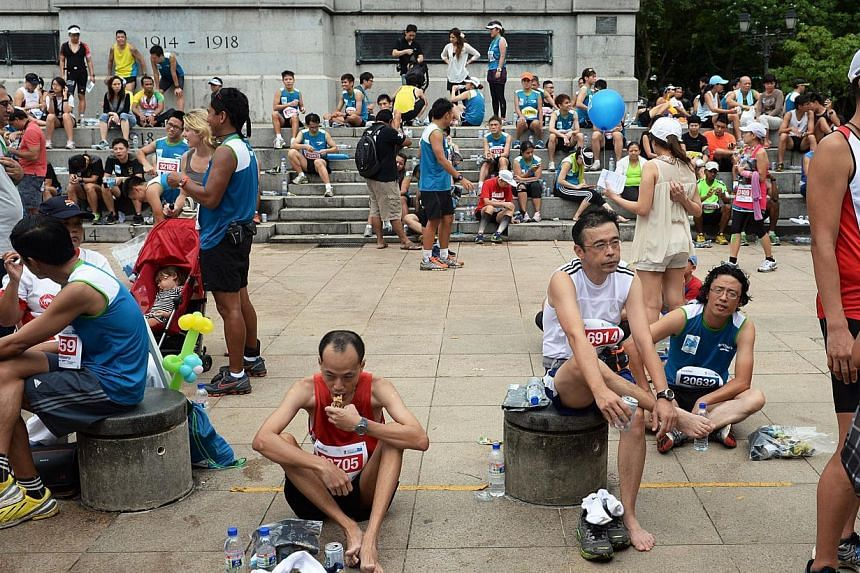 Participants resting at the Cenotaph next to the Padang aftertheStandard Chartered Marathon 2013 on Sunday, Dec 1, 2013. -- ST PHOTO:RAJ NADARAJAN