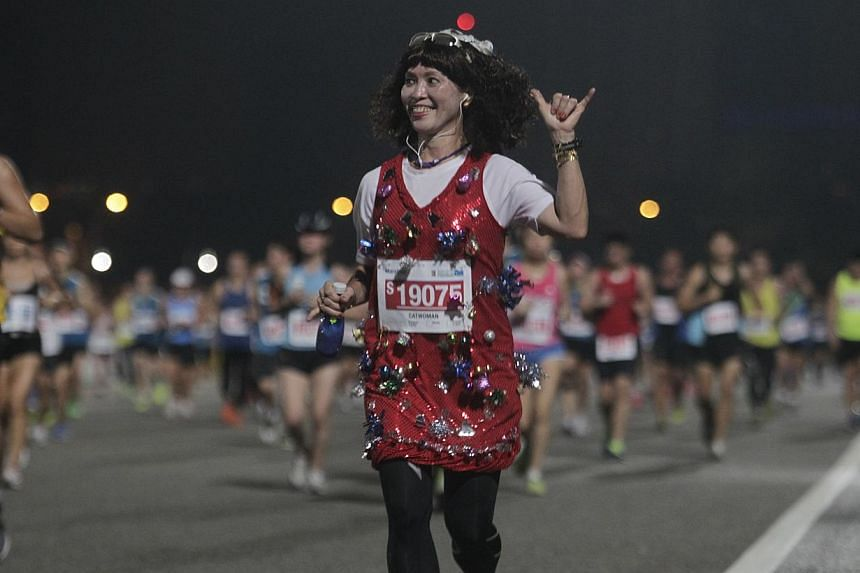 A 42.195km participant who goes by the moniker of Catwoman dresses in a Christmas-inspired attire during Standard Chartered Marathon 2013 on Sunday, Dec 1, 2013. -- ST PHOTO: KEVIN LIM