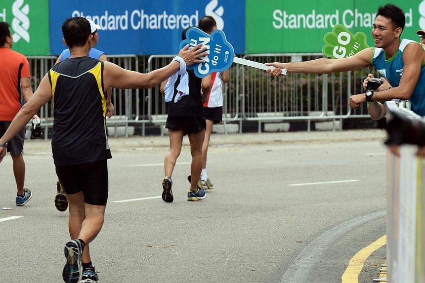 A runner being cheered on close to the finish line at the PadangduringtheStandard Chartered Marathon 2013 on Sunday, Dec 1, 2013. -- ST PHOTO:RAJ NADARAJAN