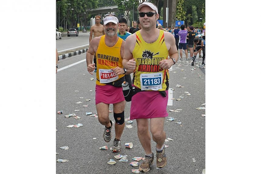 (From left) Father and son, Dave Messer, 55 (who visited from hawaii), and Chris Messer, 32, running in pink skirts for the 2nd year in a row during the Standard Chartered Marathon 2013 on Sunday, Dec 1, 2013. -- ST PHOTO: RAJ NAD