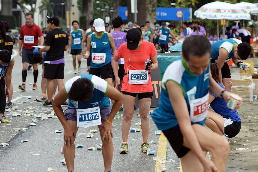 Runners slapping on muscle rub at the 40km mark, outside the F1 pit during the Standard Chartered Marathon 2013 on Sunday, Dec 1, 2013. -- ST PHOTO: RAJ NADARAJAN