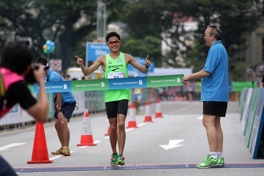 Singapore's Mok Ying Ren crosses the finish line and becomes the fastest local runner for the 42.195km Standard Chartered Marathon 2013 on Sunday, Dec 1, 2013. -- ST PHOTO: KEVIN LIM