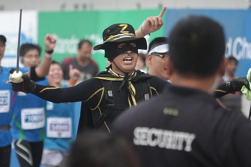 An Ekiden participant dressed as Zorro crosses the finish line during the Standard Chartered Marathon 2013 on Sunday, Dec 1, 2013. -- ST PHOTO: KEVIN LIM