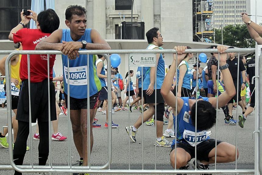 Participants of the full marathon try to come to terms with fatigue after completing the race intheStandard Chartered Marathon 2013 on Sunday, Dec 1, 2013. -- ST PHOTO:KEVIN LIM