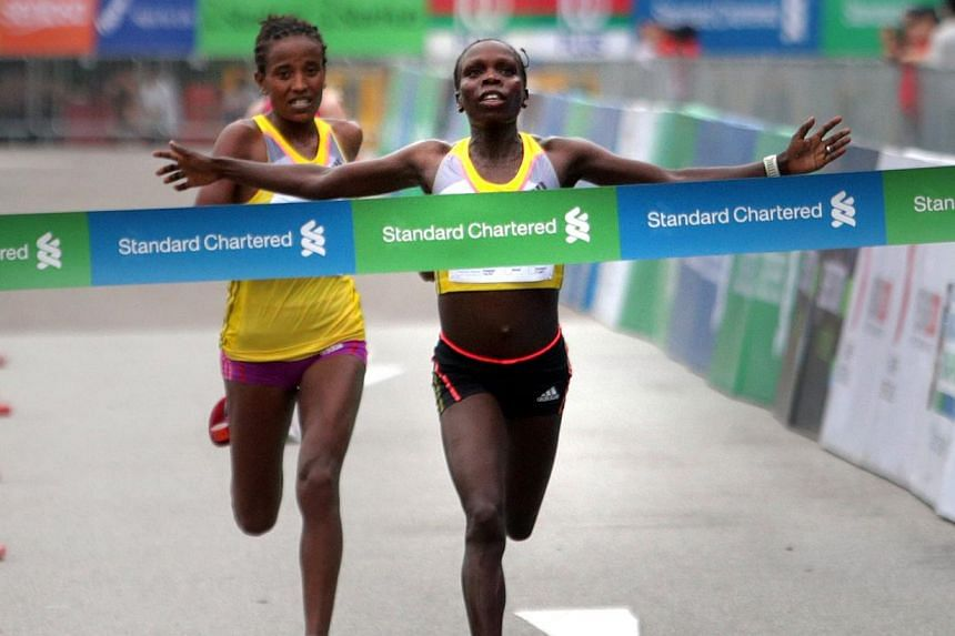 Kenyan runner Sharon Cherop crosses the finishing line and becomes the fastest woman, ahead of countrywoman Debre Godana and Russian Prokopeva Alina for the 42.195 kmStandard Chartered Marathon 2013 on Sunday, Dec 1, 2013. -- ST PHOTO:KEV