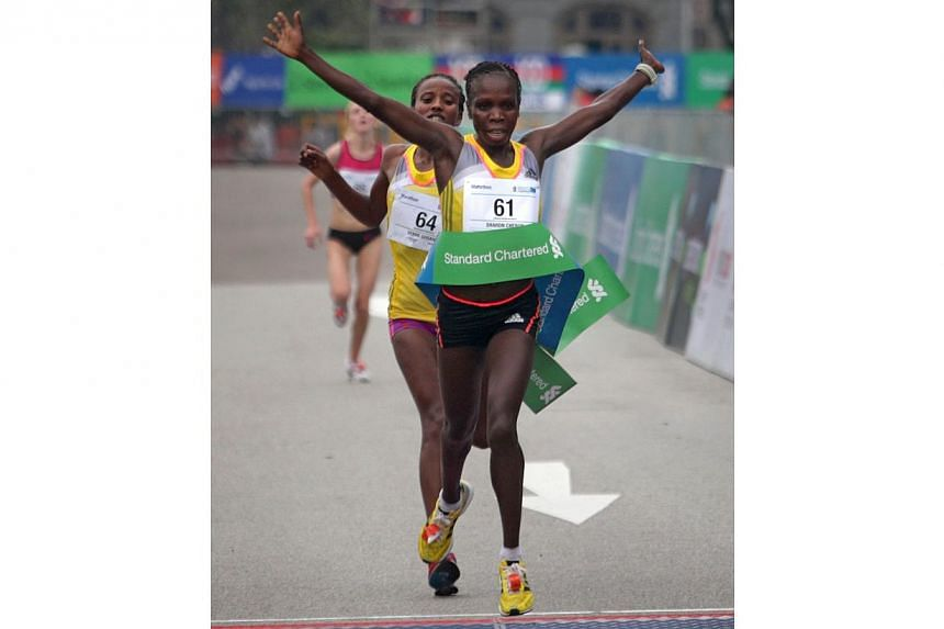 Kenyan runner Sharon Cherop crosses the finishing line and becomes the fastest woman, ahead of countrywoman Debre Godana and Russian Prokopeva Alina for the 42.195 km Standard Chartered Marathon 2013 on Sunday, Dec 1, 2013. -- ST PHOTO: KEV