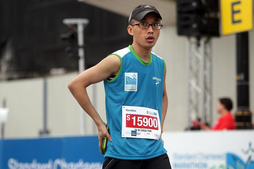 Local runner Tam Chua Puh after crossing the finishing line for the 42.195km full marathon at the Standard Chartered Marathon 2013 on Sunday, Dec 1, 2013. -- ST PHOTO: KEVIN LIM