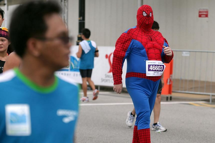 Half marathon participant David Ash, dressed as Spiderman, completes his race during the Standard Chartered Marathon 2013 on Sunday, Dec 1, 2013. -- ST PHOTO: KEVIN LIM