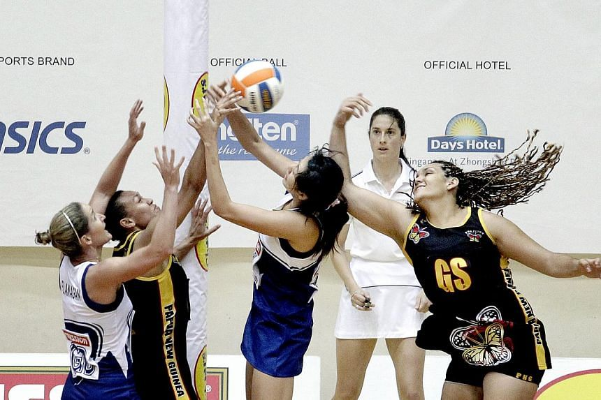 Singapore's Olivia Flanagan (extreme left) and team-mate Chen Lili defend against Papua New Guinea in their 44-43 victory at the Nations Cup on Monday, Dec 2, 2013. Singapore continued their good start at the netball Nations Cup, making it two w